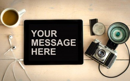 "A camera with an iPad with the text ""Your Message Here"""