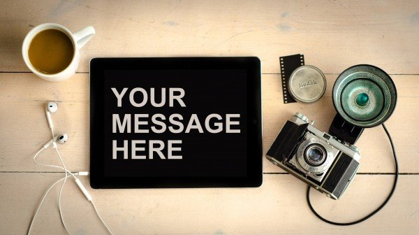 """A camera with an iPad with the text """"Your Message Here"""""""