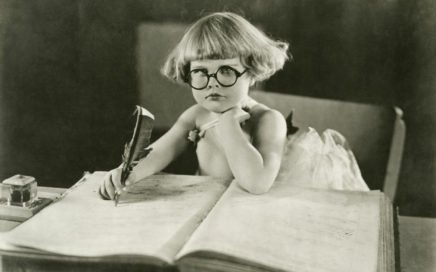 A young girl wearing round glasses and writing in a large ledger with a quill pen