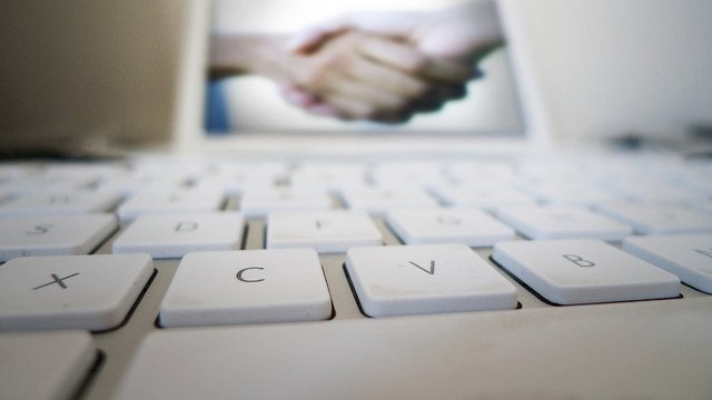 A laptop computer featuring an image of a handshake on the screen